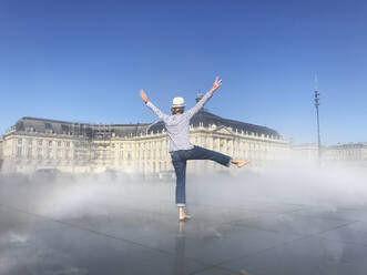Woman having fun on Miroir d'eau, Bordeaux, France - GWF06251