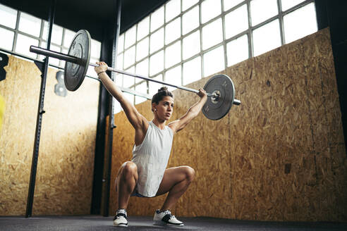 Young brunette woman doing overhead squat exercise at gym - MTBF00155