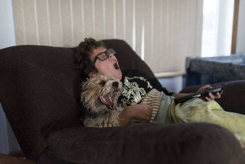 Boy and dog yawning while sitting on sofa at home - CAVF68415