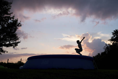 Carefree boy with arms raised jumping into swimming pool against cloudy sky during dusk - CAVF68442