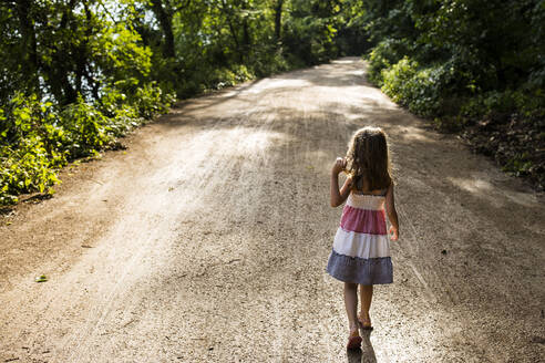 Rear view of girl walking on dirt road amidst trees in forest - CAVF68460