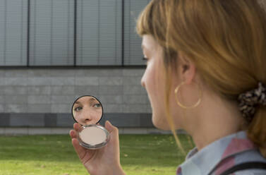 Young woman with nose piercing looking at beauty mirror in her hand - FLLF00341