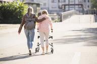 Granddaughter assisting her grandmother walking with wheeled walker - UUF19500