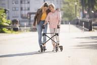 Granddaughter assisting her grandmother walking with wheeled walker - UUF19503