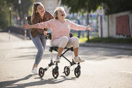 Granddaughter and her grandmother having fun with wheeled walker - UUF19512