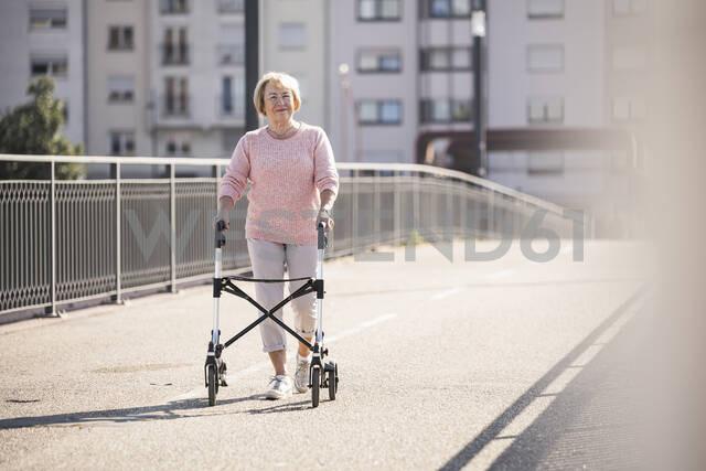Senior woman with wheeled walker on footbridge - UUF19521 - Uwe Umstätter/Westend61