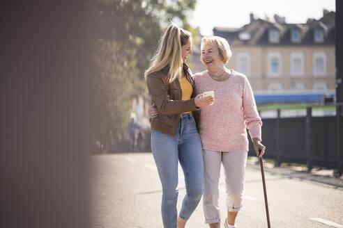 Granddaughter and her grandmother walking on footbridge and using smartphone - UUF19533