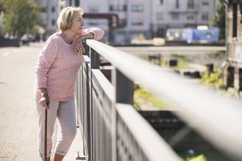 Senior woman walking on footbridge, using walking stick - UUF19536