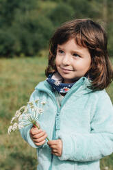 Portrait of smiling little girl with wildflower in autumn - GEMF03275