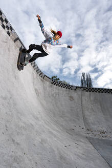 Germany, Baden-Wurttemberg, Waiblingen, Young woman skateboarding in skate park - STSF02346