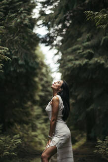 Young woman wearing white dress in the forest - MTBF00156