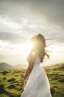Young woman wearing white dress on viewpoint at sunset - MTBF00165