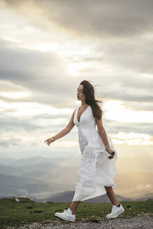 Young woman wearing white dress on viewpoint at sunset - MTBF00171