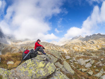 Hiker sitting on a mountain enjoying the view, nature park Adamello, Italy - LAF02408