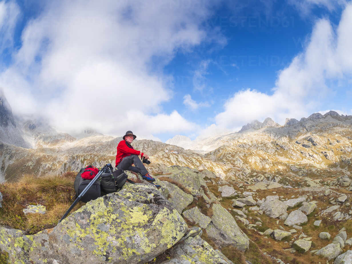 Hiker sitting on a mountain enjoying the view, nature park Adamello, Italy - LAF02408 - Albrecht Weißer/Westend61