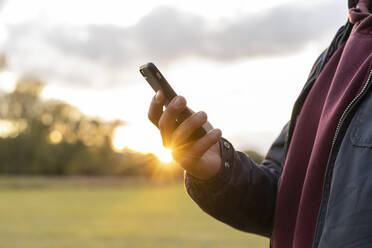 Man standing in rural landscape during sunset and holding a smartphone - AFVF04162