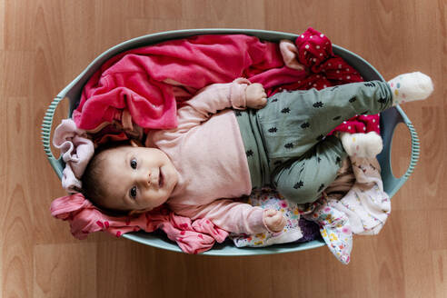 Baby girl in the laundry basket with clothes to clean - GEMF03287