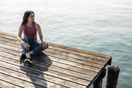 Young woman sitting on jetty looking at distance, Lake Starnberg, Germany - WFF00151