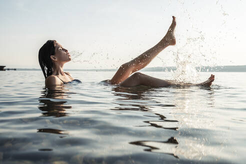Young woman bathing in Lake Starnberg, splashing with water, Germany - WFF00160