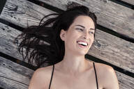 Portrait of laughing young woman relaxing on jetty - WFF00163