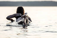 Back view of young woman lying on surfboard by sunset, Lake Starnberg, Germany - WFF00166