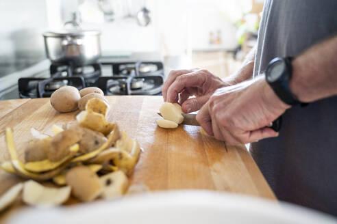 Senior man cutting potatoes on the chopping board - AFVF04165
