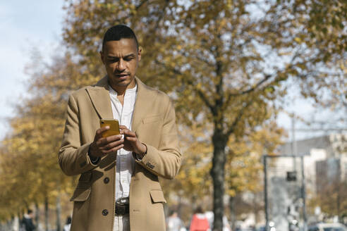 Portrait of businessman looking at cell phone in autumn - AHSF01076
