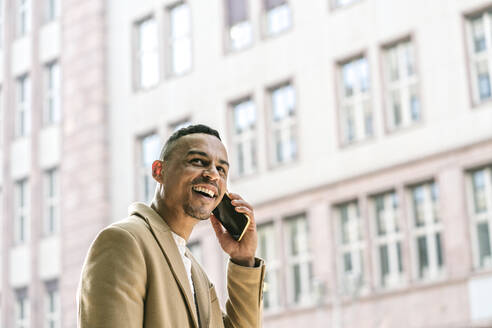Portrait of laughing businessman on the phone in the city - AHSF01079