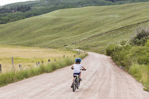 Rear view of 5 year old boy biking on country road - MINF12768