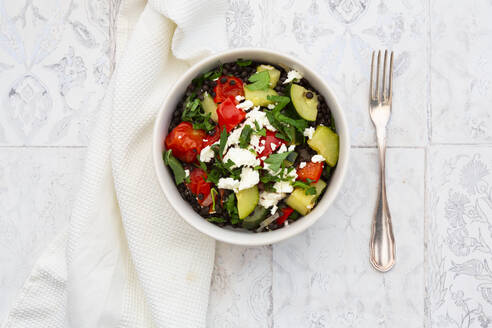 Bowl of salad with beluga lentils, tomatoes, paprika, zucchini, feta cheese, mint and parsley - LVF08424