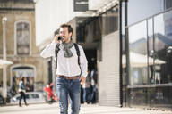 Smiling young man with backpack on the phone in the city - UUF19575