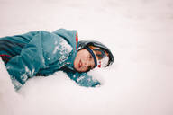 Thoughtful boy lying in snow during winter - CAVF68778