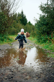 Girl standing in puddle and making spray in forest - CAVF68817