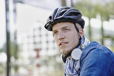 Portrait of student with cycling helmet  and headphones - RORF01950