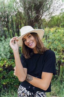 Portrait of smiling young woman with tattoo wearing summer hat in nature - AFVF04181