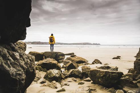 Young woman wearing yellow rain jacket at the beach at rock cave, Bretagne, France - UUF19649