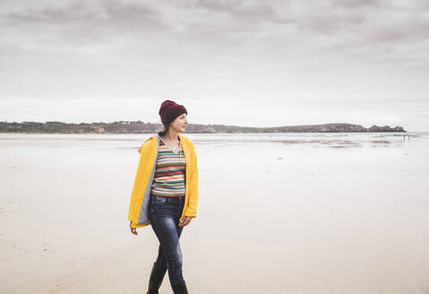 Young woman wearing yellow rain jacket at the beach, Bretagne, France - UUF19655