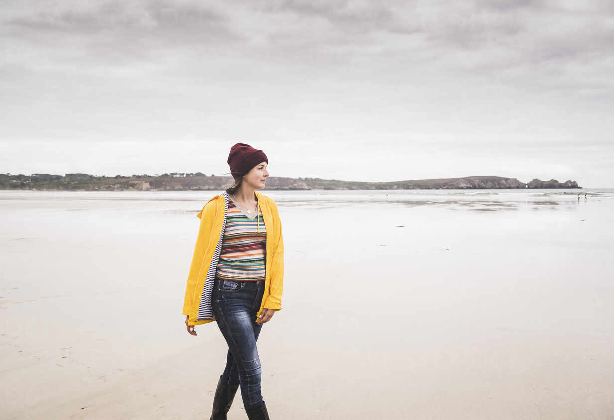 Young woman wearing yellow rain jacket at the beach, Bretagne, France - UUF19655 - Uwe Umstätter/Westend61