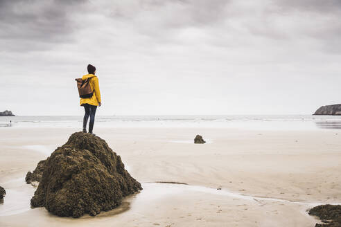 Young woman wearing yellow rain jacket at the beach, Bretagne, France - UUF19658