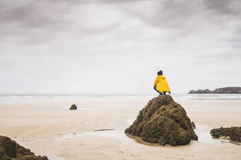 Young woman wearing yellow rain jacket at the beach, Bretagne, France - UUF19661