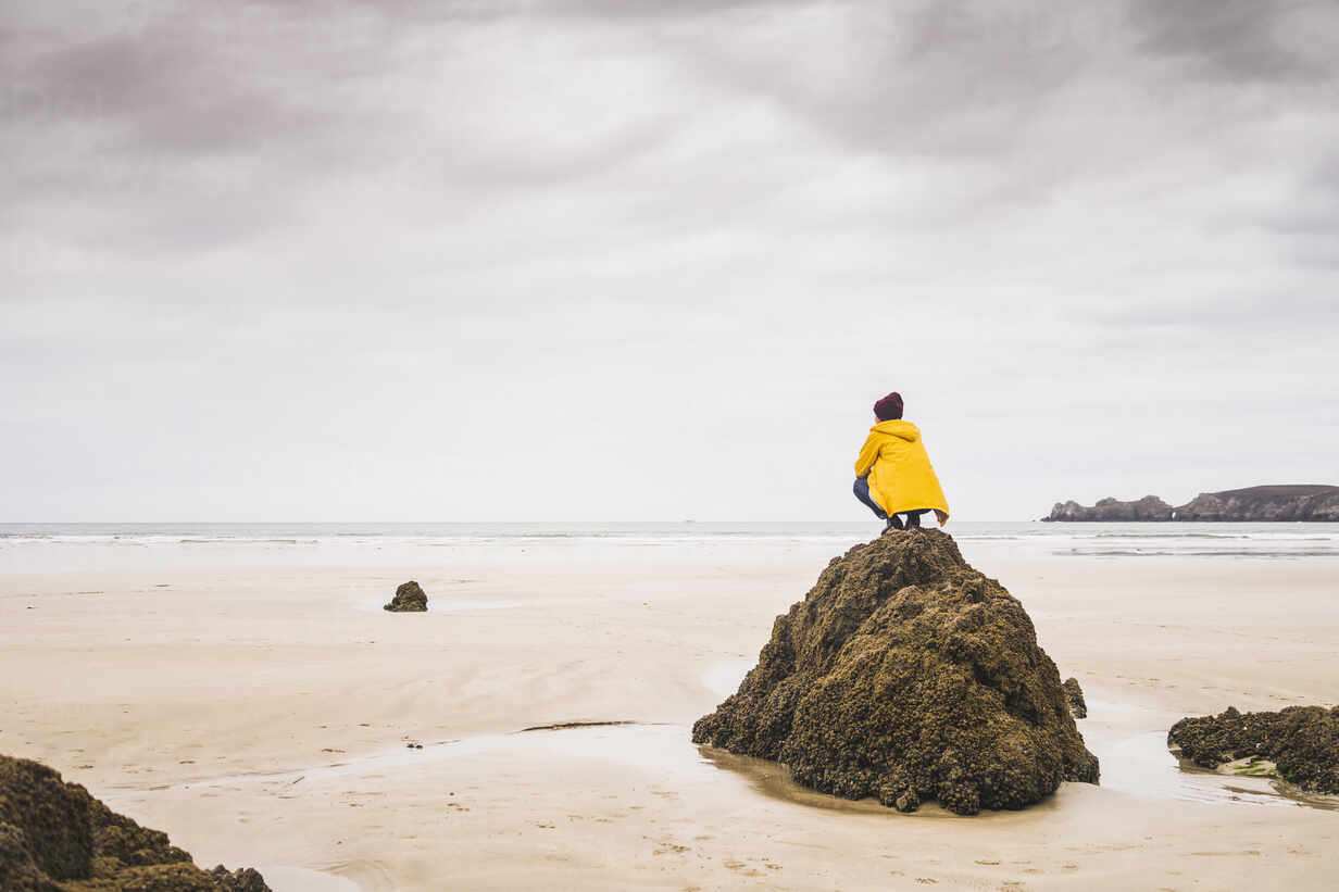Young woman wearing yellow rain jacket at the beach, Bretagne, France - UUF19661 - Uwe Umstätter/Westend61