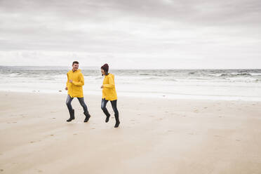 Young woman wearing yellow rain jackets and running at the beach, Bretagne, France - UUF19670
