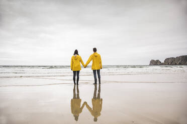 Young woman wearing yellow rain jackets and standing at the beach, Bretagne, France - UUF19673