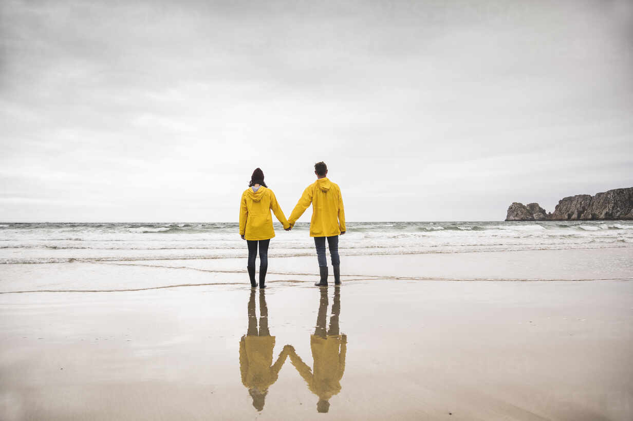 Young woman wearing yellow rain jackets and standing at the beach, Bretagne, France - UUF19673 - Uwe Umstätter/Westend61