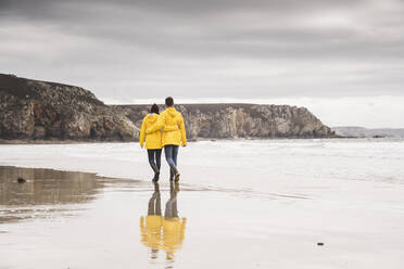 Young woman wearing yellow rain jackets and walking along the beach, Bretagne, France - UUF19676