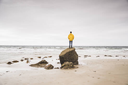 Young man wearing yellow rain jacket at the beach and standing on rock, Bretagne, France - UUF19679