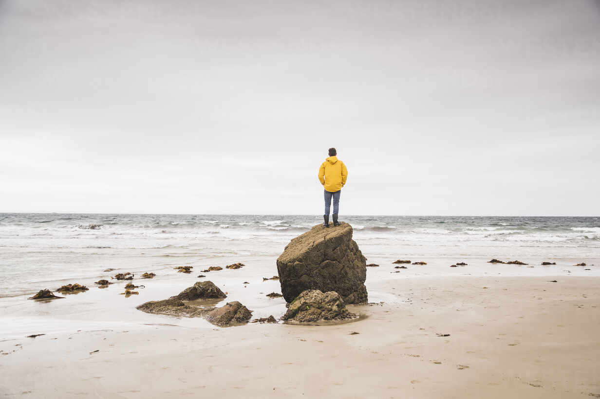 Young man wearing yellow rain jacket at the beach and standing on rock, Bretagne, France - UUF19679 - Uwe Umstätter/Westend61