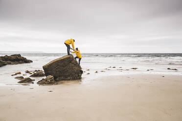 Young woman wearing yellow rain jackets and climbing on a rock at the beach, Bretagne, France - UUF19682
