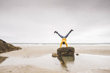 Young man wearing yellow rain jacket at the beach and doing a handstand on rock, Bretagne, France - UUF19691