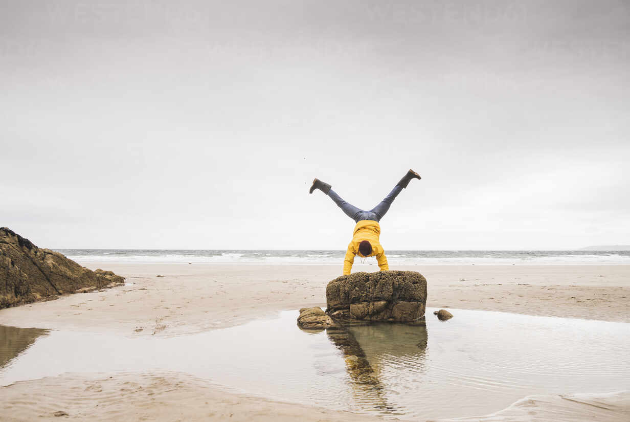 Young man wearing yellow rain jacket at the beach and doing a handstand on rock, Bretagne, France - UUF19691 - Uwe Umstätter/Westend61